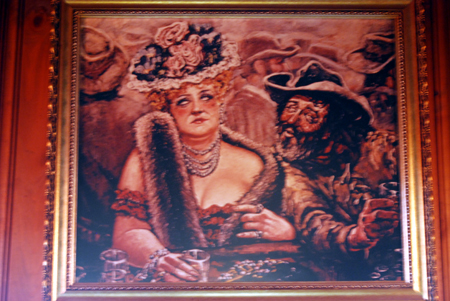 Painting of a cowboy and dressed up lady in a western saloon on display at the Winchester Cafe